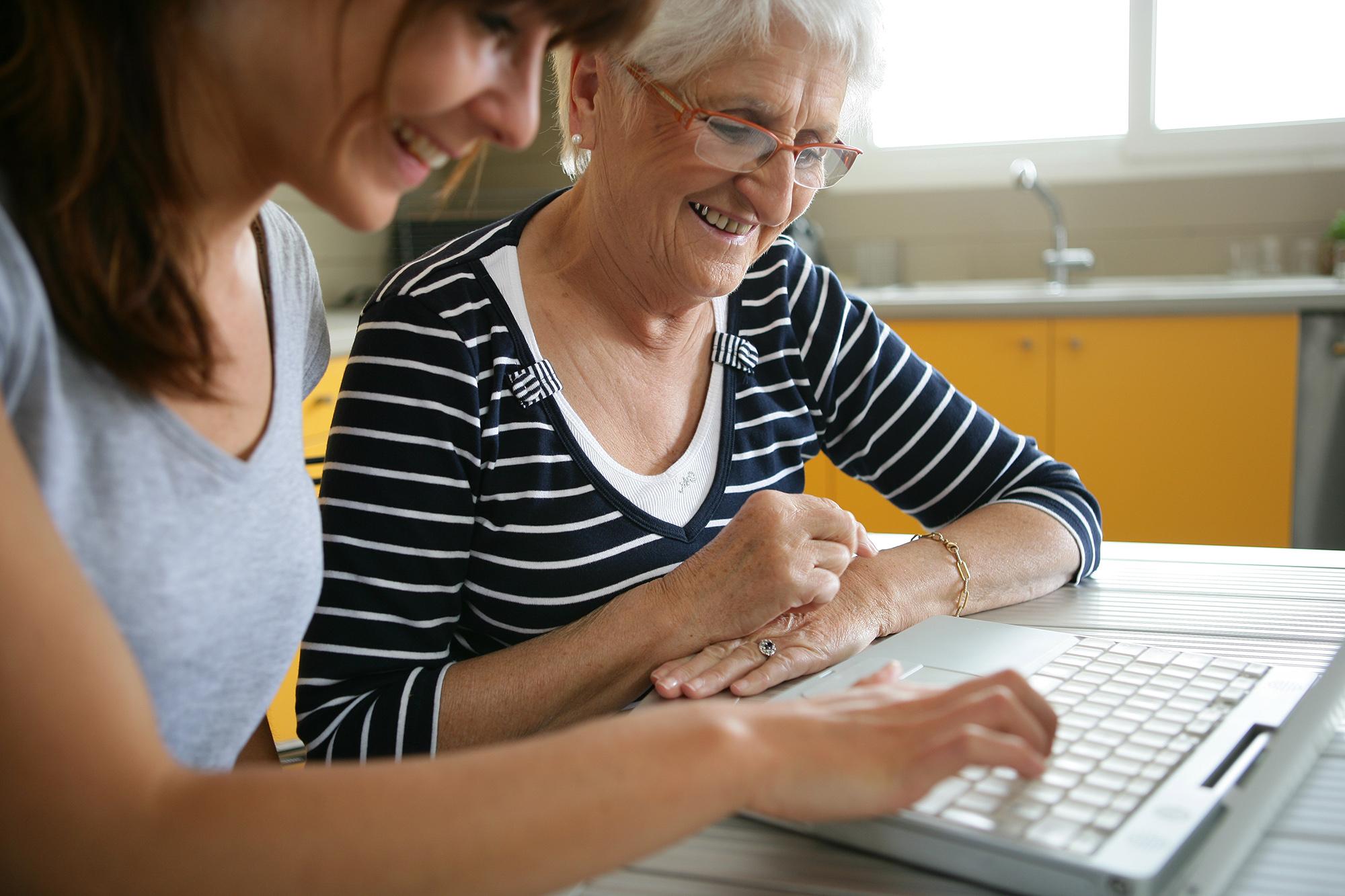 Retraitée souriante devant un ordinateur près d'une femme